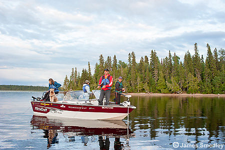 Family fishing from their fishing boat on a lake in Northern Ontario.