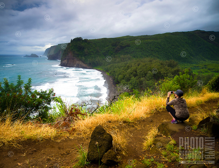 A young woman takes a picture of Pololu Valley and its beach with her smart phone from a hiking trail, Hawi, Island of Hawai'i.