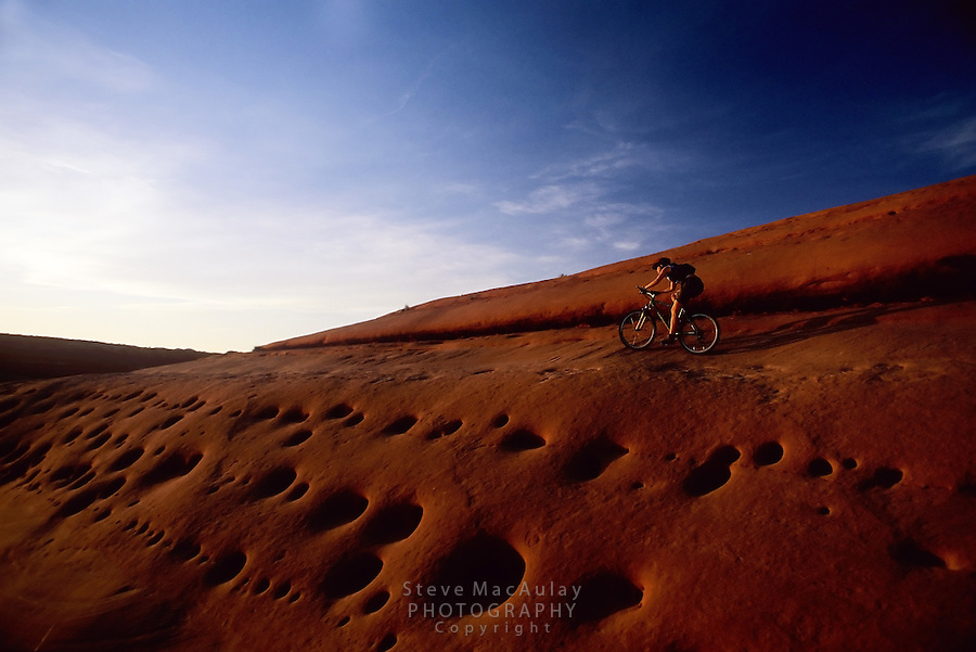 Mountain biker riding by wildly pocketed slickrock slope at sunset, Bartlet Wash, Moab, Utah