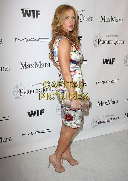POPPY MONTGOMERY.3rd Annual Women In Film Pre-Oscar Party held At A Private Residence, Bel Air, California, USA..March 4th, 2010.full length sleeveless dress side floral red white blue print flower ruched gold clutch bag beige peep silk satin toe shoes .CAP/ADM/KB.©Kevan Brooks/AdMedia/Capital Pictures.