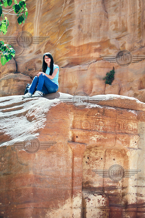 A girl sits above an inscription in a rock in the ancient city of Petra.