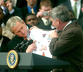 Washington, D.C. - February 14, 2006 -- United States President George W. Bush, left, looks at a jersey presented to him by Head Coach Mack Brown, right, during the South Lawn event welcoming the 2005 National Collegiate Athletic Association (NCAA) Division 1A National Football Champion Texas Longhorns to the White House in Washington, D.C. on February 14, 2006.<br /> Credit: Ron Sachs / CNP