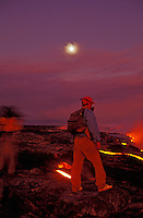Two people standing on lava fields at Kilauea Volcano with the sun almost masked by thick gaseous emissions.