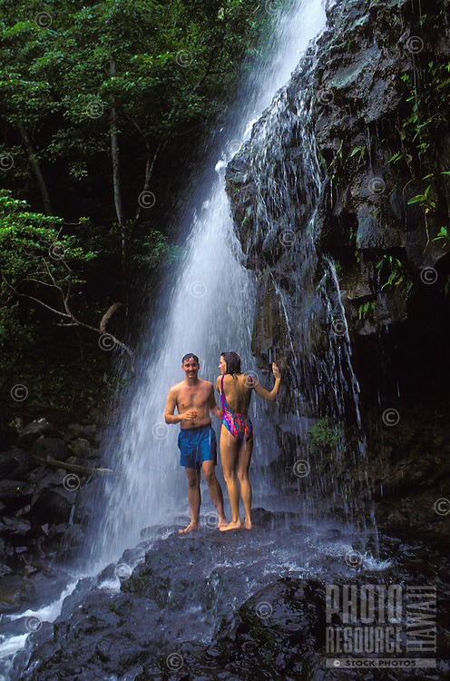 Couple standing under Kalihiwai waterfall which is owned by Princeville Ranch stables.