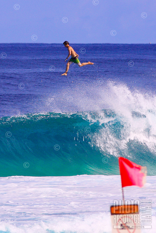 A surfer is projected up in the air and over the wave at Ehukai Beach Park on Oahu's North Shore.