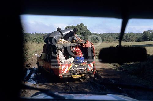 "Lolgorian, Kenya. Battered pick-up truck on muddy road with passengers, plastic drums on top, ""The True Taste of Kenya"" on back."