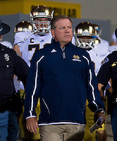 Head coach Brian Kelly leads his players onto the field for the second half.