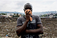 A relative of Isafu Bagua, recently deceased, holds a cloth to his face at the King Tom Cemetery. Due to the rapid increase in burials the cemetery is being enlarged and parts of a nearby rubbish dump is also being used to bury the dead.