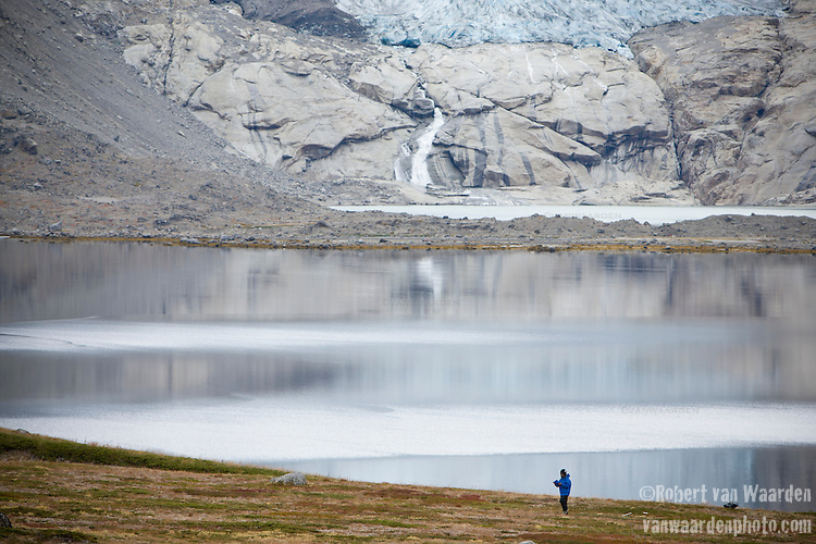A woman walks along the shore of Tasermiut Fjord in Southern Greenland. The woman is part of the Cape Farewell Youth Expedition that was organized by the British Council of Canada. In the background, a receding glacier.