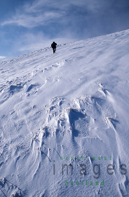 Winter snow Scottish hills hill walker climbing Lochcraig Head in the Grey Mares Tail Nature Reserve in the Moffat Hills Scotland UK