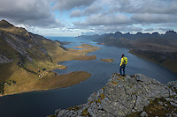 Female hiker takes in view over Selfjord from summit of Tverrfjellet, Lofoten Islands, Norway