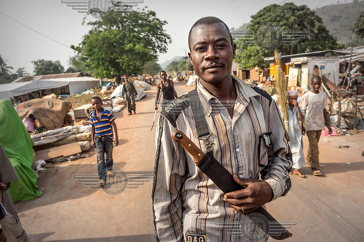 A man, armed with a machete, in a Muslim district that is under the protection of the French army. The residents have gathered at a mosque while they wait to be evactuated but they have armed themselves against any incursions by those seeking to attack them. In 2013 a rebellion by a predominantly Muslim rebel group Seleka, led by Michel Djotodia, toppled the government of President Francios Bozize. Djotodia declared that Seleka would be disbanded but as law and order collapsed the ex-Seleka fighters roamed the country committing atrocities against the civilian population. In response a vigillante group, calling themselves Anti-Balaka (Anti-Machete), sought to defend their lives and property but they then began to take reprisals against the Muslim population and the conflict became increasingly sectarian. French and Chadian peacekeeping forces have struggled to contain the situation and the smaller Muslim population began to flee the country.