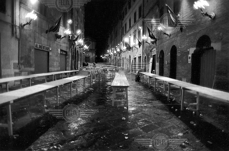 © Francesco Cito / Panos Pictures..Siena, Tuscany, Italy. The Palio. ..The aftermath of one of the banquets held on the evening before the race...Twice each summer, the Piazza del Campo in the medieval Tuscan town of Siena is transformed into a dirt racetrack for Il Palio, the most passionately contested horse race in the world. The race, which lasts just 90 seconds, has become intrinsic to the town's heritage since it was first run in 1597...
