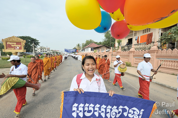 Nith Nitikar, an 18-year old student, walks with musicians and Buddhist monks and nuns to lead a march commemorating World AIDS Day in Battambang, Cambodia. Among sponsors of the march was the Salvation Centre Cambodia, an organization that works with Buddhist monks and other activists to foster support for people living with HIV and AIDS as well as public education and advocacy throughout the country.
