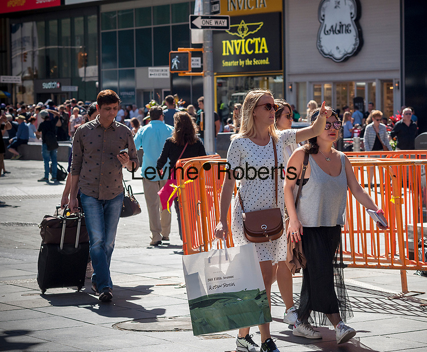 Visitor to Times Square in New York with her & Other Stories purchases on Thursday, September 15, 2016.  U.S. retail sales for August were below analysts' expectations as automobile and gasoline sales were weak and shoppers abandoned their spending spree from the spring.  (© Richard B. Levine)