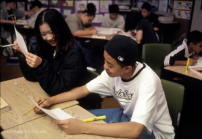 Albany CA Junior high school English students socialzing while reading each other's writing in class