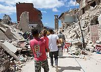 People walk past rubble of collapsed buildings in the village of Amatrice, central Italy, hit by a magnitude 6 earthquake at 3,36 am, 24 August 2016.<br /> Una veduta delle macerie degli edifici crollati dopo il terremoto che alle 3,36 del mattino ha colpito Amatrice, 24 agosto 2016.<br /> UPDATE IMAGES PRESS/Riccardo De Luca