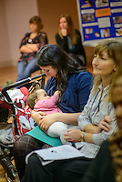 "A mother breastfeeding her baby at a conference.<br /> <br /> Image from the breastfeeding collection of the ""We Do It In Public"" documentary photography picture library project: <br />  www.breastfeedinginpublic.co.uk<br /> <br /> <br /> Middlesex, England, UK<br /> 2016<br /> <br /> © Paul Carter / wdiip.co.uk"