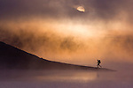 A photo of a man hiking along the shore of a foggy lake at sunrise near Truckee, CA.