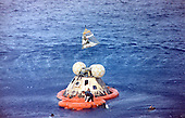 Astronaut John L. Swigert Jr., command module pilot, is lifted aboard a helicopter in a Billy Pugh helicopter rescue net while astronaut James A. Lovell Jr., commander, awaits his turn. Astronaut Fred W. Haise, Jr., lunar module pilot, is already aboard the helicopter. In the life raft with Lovell, and in the water are several U.S. Navy underwater demolition team swimmers, who assisted in the recovery operations. The crew was taken to the U.S.S. Iwo Jima, prime recovery ship, several minutes after the Apollo 13 spacecraft splashed down at 12:01:44 pm CST on April 17, 1970..Credit: NASA via CNP