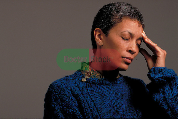 woman standing and massaging forehead
