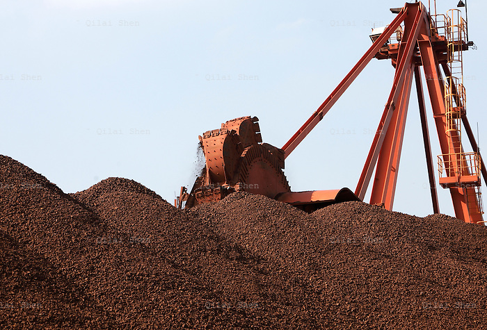 A conveyer belts dumps iron ore onto a pile at a transfer and storage center operated by the Shanghai International Port Group in Shanghai, China on 26 January 2010. China's economic boom and hunger for natural resources has been a blessing for countries such as Australia and Brazil, who controls most the world's high quality iron ore deposits.