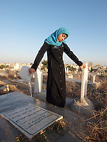 "Amira Al-Qerem (16) washes the grave of her father, sister and brother in Gaza City on October 26 2010. Amira was missing and presumed dead after she was injured by one of the same explosions that killed her father, brother and sister during the last days of the Israeli invasion of Gaza in 2009. She was found three days later, after her family thought they had buried her remains with those of the other three. She is one of the main subjects of the controversial documentary film ""Tears of Gaza"" by director Vibeke Løkkeberg."