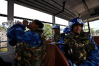 Indian female Peacekeepers from the Indian FPU ( formed police unit ) mount on their vehicle after providing armed  support to the liberian national police ( in the background ) during a cordon and search operation in Monrovia, Liberia on Monday March 19 2007. .103 Indian police personnel  were specially selected to take part in the UNMIL peacekeeping mission in Liberia for an initial deployment of 6 months. .They are the first contingent entirely formed by women in the history of the United Nations Peacekeeping..their mission in the country is to provide fire support to the unarmed liberian security forces. In india these women distinguished themselves by operating in the most troubled areas of the country taking part in counter insurgency and crowd control special operations.
