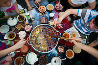 A group eats hotpot out of a split, or yuanyang, pot separating spicy broth from not spicy at An Pang hotpot in an alley above Tiyu Road in central Yuzhong district, Chongqing, China.