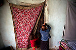 Fahima, 12, and Rika, 3, answer the door of the room that is their home in the neighborhood of Shahre Kohneh, Kabul, Afghanistan, Monday, Apr. 6, 2009. The girls' mother is addicted to heroin and opium.