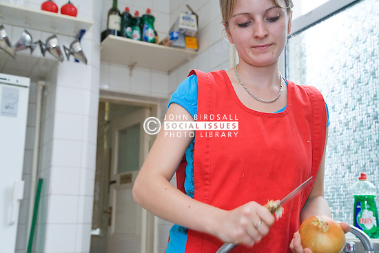 Young cook peeling an onion in kitchen of Polish Social Club,
