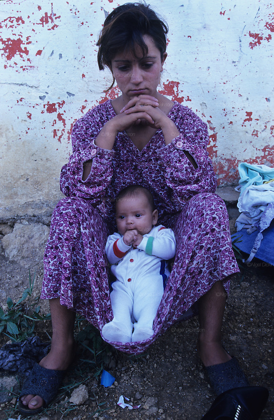 A Roma teenage girl and her baby, refugees from the Kosovo War. They make a living the best they can, scavenging the markets and begging. They were unable to afford a Mafia boat trip from the Balkans to Western Europe. Bar, Montenegro 1999.