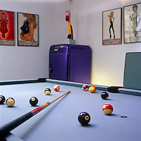 The pool room is accessorised by a dark purple fridge and is located off the entrance hall