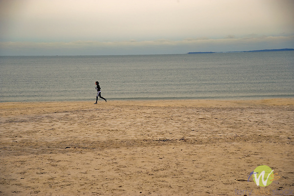 Woman running on beach Long Island Sound.