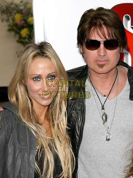 "TISH CYRUS (Leticia) & BILLY RAY CYRUS.at  the World Premiere of ""The Spy Next Door"" held The Grove in Los Angeles, California, USA, January 9th, 2010..portrait headshot black leather jacket  grey gray married couple husband wife  soul patch facial hair necklaces make-up eyeliner                                                           .CAP/RKE/DVS.©DVS/RockinExposures/Capital Pictures"