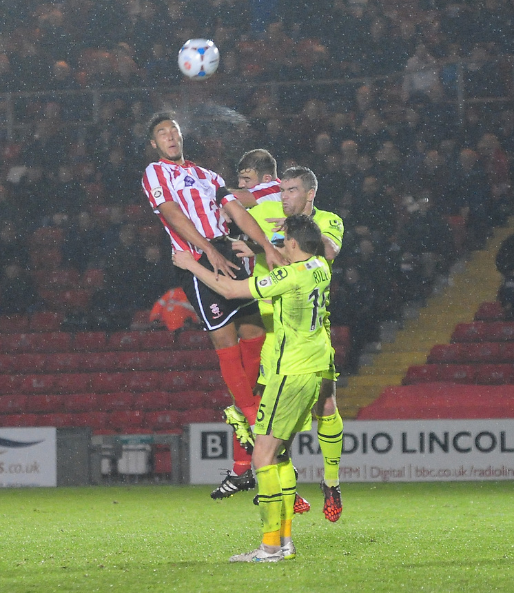 Lincoln City&rsquo;s Kyle Wootton goes up fir a header with Tranmere Rovers' Martin Riley and Tranmere Rovers&rsquo; Steve McNulty<br /> <br /> Photographer Andrew Vaughan/CameraSport<br /> <br /> Football - Vanarama National League - Lincoln City v Tranmere Rovers - Saturday 14th November 2015 - Sincil Bank - Lincoln<br /> <br /> &copy; CameraSport - 43 Linden Ave. Countesthorpe. Leicester. England. LE8 5PG - Tel: +44 (0) 116 277 4147 - admin@camerasport.com - www.camerasport.com