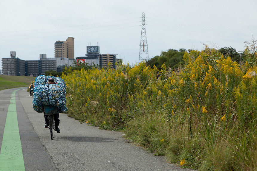 A homeless man cycles along the banks of the Arakawa River near Kita Senju, with his bicycle piled high with aluminium cans that he will sell to recycling firms. Tokyo, Japan Friday October 12th 2012