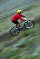 Woman mountain biking, blurred motion, Rocky Mountains, Colorado. Kim Clark (MR 671). Colorado.