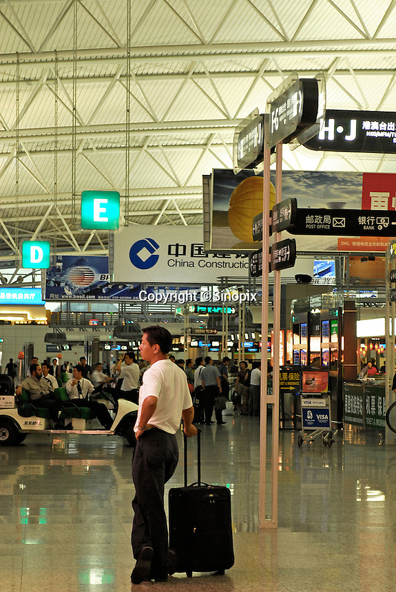 A man is waiting at the departure hall for the flight to take off. Guangzhou's Baiyun International Airport, .G.uangzhou, China. The new airport has received over 23.5 million passengers this year and it has become one of the top 50 airports in the world. The south China air hub is going to inaugurate 50 new international lines in the coming five years. In 2006-2010, the provincial airport group plans to invest 11.4 billion yuan to expand the airport. The airport aims to become world's top 20 airport by the year 2015..