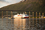Hurtigruten ferry ship Nordlys approaching Tromso passing under cantilever bridge, Norway