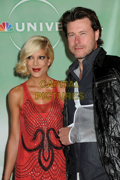 TORI SPELLING & DEAN McDERMOTT.NBC Universal Press Tour Cocktail Party held at the Langham Hotel, Pasadena, California, USA, 10th January 2010..half length red sleeveless dress married couple husband wife black leather jacket arm in sling injured injury sheer mesh beaded pattern .CAP/ADM/BP.©Byron Purvis/AdMedia/Capital Pictures.