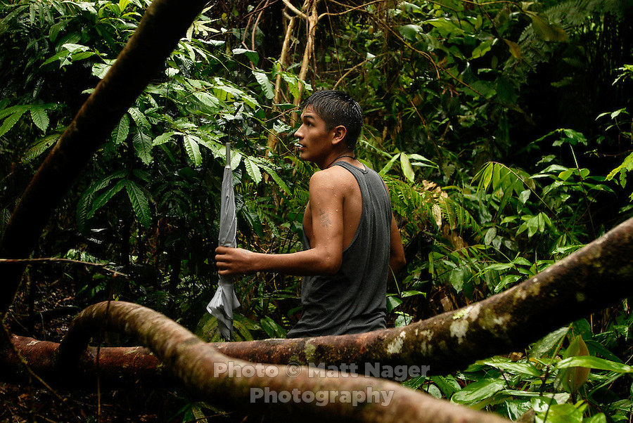 Rene Uribe looks at the sky for rain while passing through the rain forest with his umbrella in Eterezama, Boliva.
