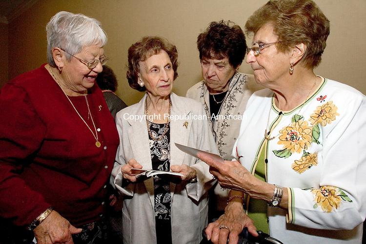 WATERBURY, CT- 26 SEPTEMBER 2008 --092608JS04--Members of the Waterbury Catholic High School class of 1943, from left, Lucy Christiano of Waterbury, Mary Gentile of Waterbury, Ruth Hutt of Wolcott and Vita Saginario of Watertown, look over old photographs during the 65th class reunion Friday at the Courtyard by Marriott in Waterbury. <br /> Jim Shannon / Republican-American