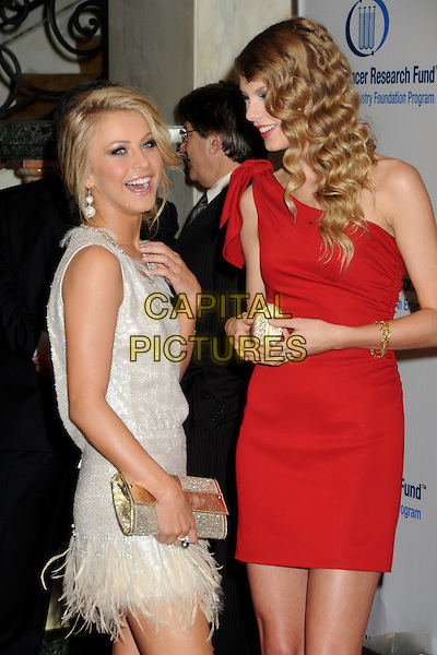JULIANNE HOUGH & TAYLOR SWIFT  .EIF's Women's Cancer Research Fund Benefit held at the Beverly Wilshire Hotel, Beverly Hills, California, USA..January 27th, 2010.half length red one shoulder wavy hair dress gold white silver sleeveless feathers clutch bag profile laughing.CAP/ADM/BP.©Byron Purvis/AdMedia/Capital Pictures.