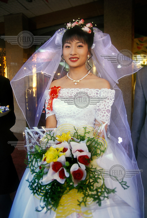 Bride on her wedding day wearing a western-style white bridal gown as she waits to greet guests to her reception.