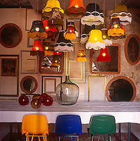 A collection of old fashioned lamp shades hang from the ceiling above a long dining table with white cloth. A collection of mirrors and picture frames are arranged on one wall.
