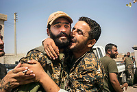 August 2017. Raqqa, Syria.<br /> A shellshocked MFS soldier is greeted with hugs and kisses as he returns back from fighting ISIS on the western front lines of Raqqa, Syria.<br /> The MFS (Syriac Military Council) are a group of Assyrian Christians who fight alongside the Syrian Democratic Forces in the fight to topple ISIS.<br /> Photographer: Rick Findler