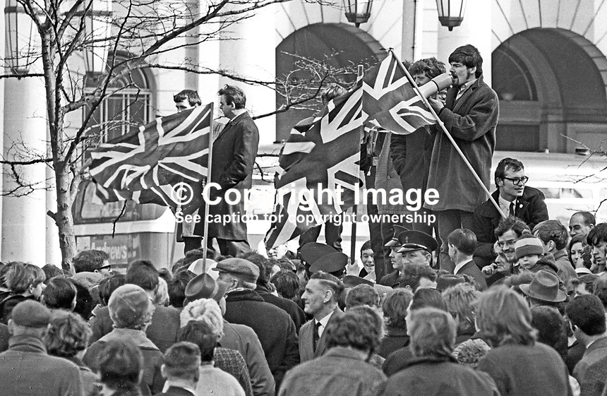 People's Democracy leader Kevin Boyle attempting to address supporters at a meeting in the grounds of Belfast City Hall, N Ireland, on 22nd March 1969. Speakers were continually heckled by loyalists protesting against the meeting. Union Jacks were also continually waved in front of the speakers. The meeting was eventually abandoned. 196903220137a<br /> <br /> Copyright Image from Victor Patterson,<br /> 54 Dorchester Park, Belfast, UK, BT9 6RJ<br /> <br /> t1: +44 28 90661296<br /> t2: +44 28 90022446<br /> m: +44 7802 353836<br /> <br /> e1: victorpatterson@me.com<br /> e2: victorpatterson@gmail.com<br /> <br /> For my Terms and Conditions of Use go to<br /> www.victorpatterson.com