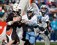 Matt Dolente (4) of Johns Hopkins tries to keep Tyler Moni (27) of Princeton away from the goal during the Face-Off Classic in at M&T Stadium in Baltimore, MD