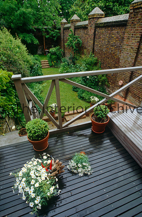 A wooden staircase leads down to the garden from the balcony outside the master bedroom